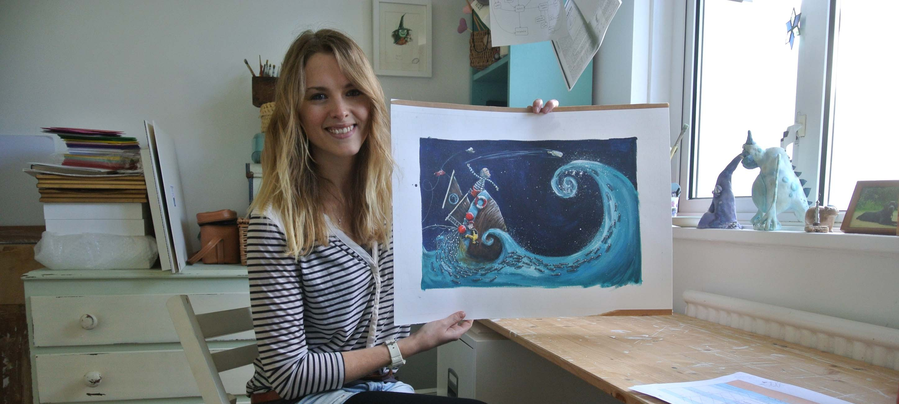Zoe with an image from her children's book, 'The Lighthouse Keeper'